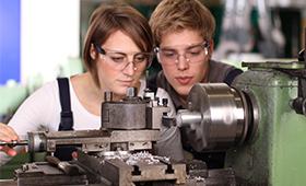 Abbildung: Ausbildungssituation - ein junger Mann und eine junge Frau arbeiten an einer Fräse
