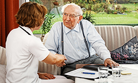 Nurse talking to elderly man