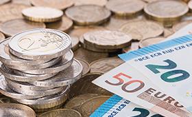Euro-Geldscheine und gestapelte Münzen