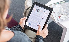 Frau mit Laptop betrachtet die Internetseite überaus.de