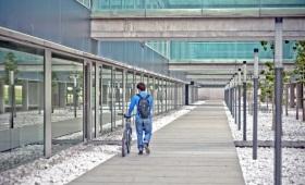 Ein einsamer Student schiebt sein Fahrrad über ein menschenleeres Campusgelände.