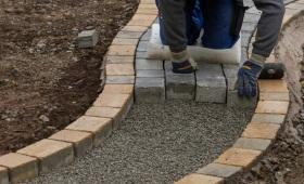 Ein knieender Pflasterer pflastert einen halb fertig gestellten Pflasterweg mit Pflastersteinen.