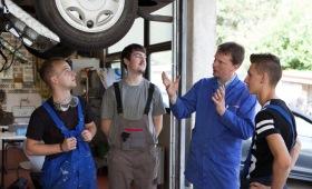 Drei Auszubildende und ein Ausbilder unter einem Auto
