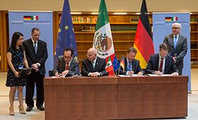 Foto: Teilnehmende unterschreiben eine Erklärung zur Zusammenarbeit