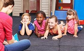 Kinder im Kindergarten, betreut von einer Erzieherin