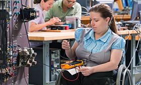 Foto: Rollstuhlfahrerin arbeitet an Elektroinstallationen