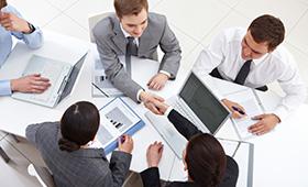 Gruppe von Menschen in einer Arbeitssituation am Schreibtisch, von denen sich zwei über den Tisch die Hand reichen