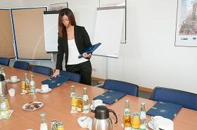 Eine Veranstaltungskauffrau bestückt einen Sitzungssaal mit Programmheften
