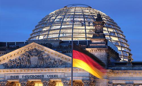 Reichstagsgebäude in der Dämmerung, davor eine deutsche Fahne im Wind wehend